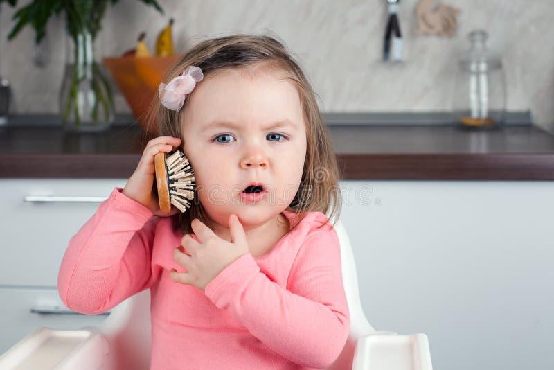 Flicka 2 år gammalt spela med en hemmastadd hårkam - beskriva en emotionell konversation på telefonen royaltyfri fotografi