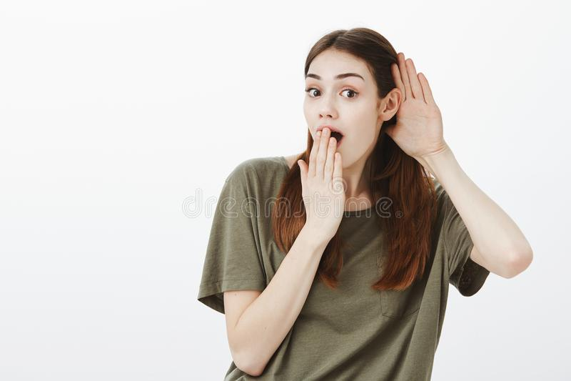 Flicka alla öron som lyssnar varmt rykte Inomhus skott av den positiva charmiga kvinnlign i tillfällig dräkt som böjer in mot kam arkivfoton