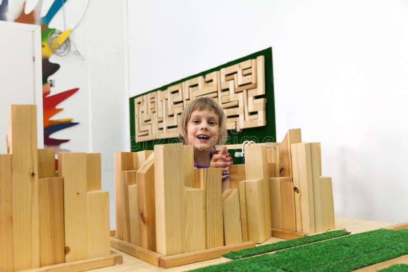 Flicka av 5 år gammalt spela med träpusslet royaltyfria foton