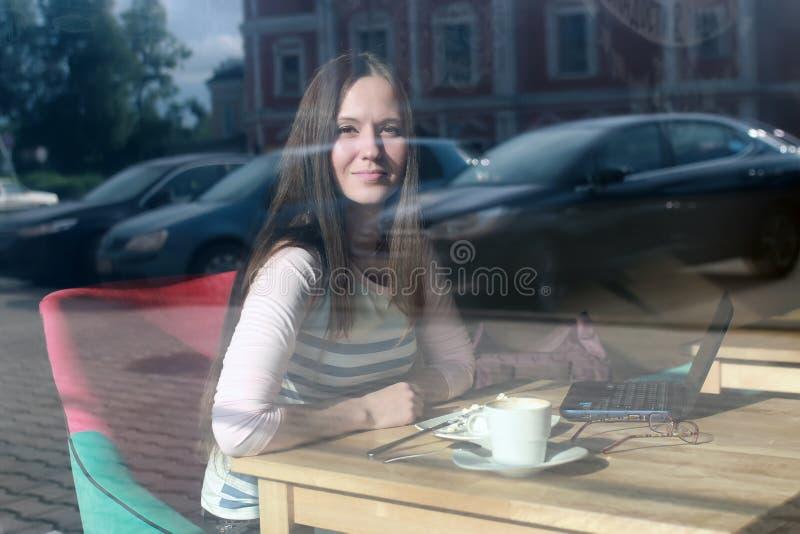 Flicka bak exponeringsglas i kafé royaltyfri bild