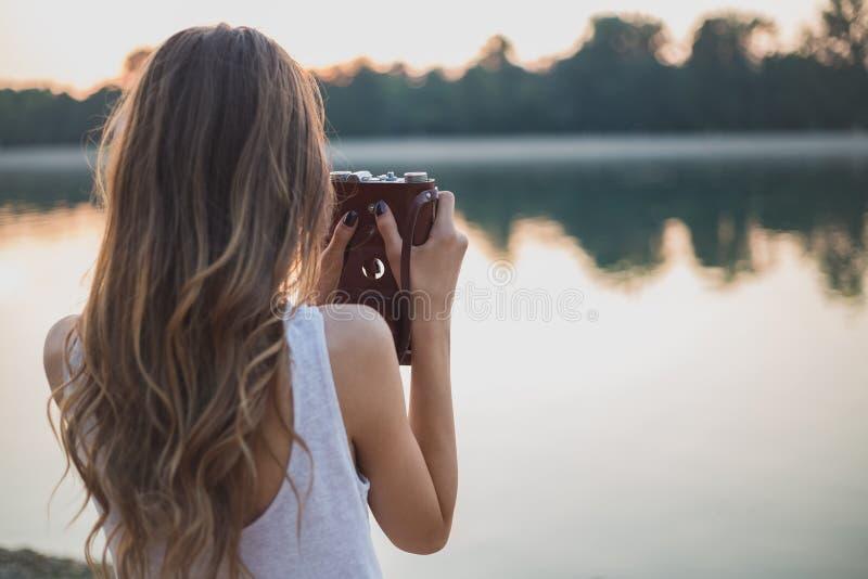 Flicka bakifrån som fotograferar på stranden arkivfoton