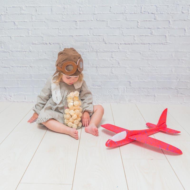 Flicka, barn i hjälmen av piloten med flygplanet och lig arkivbild