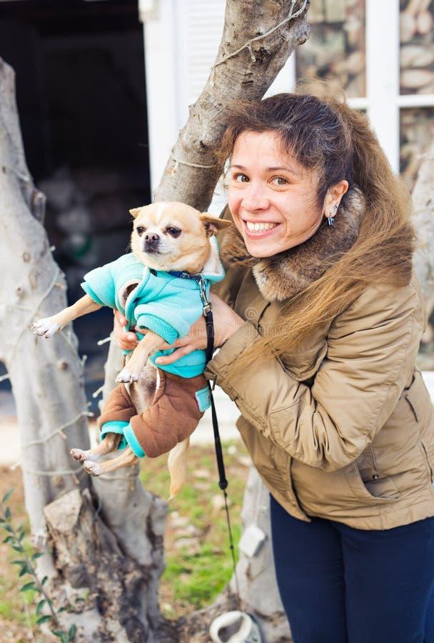 Flicka eller kvinna som utomhus rymmer den gulliga chihuahuahunden - folket daltar begrepp arkivbilder