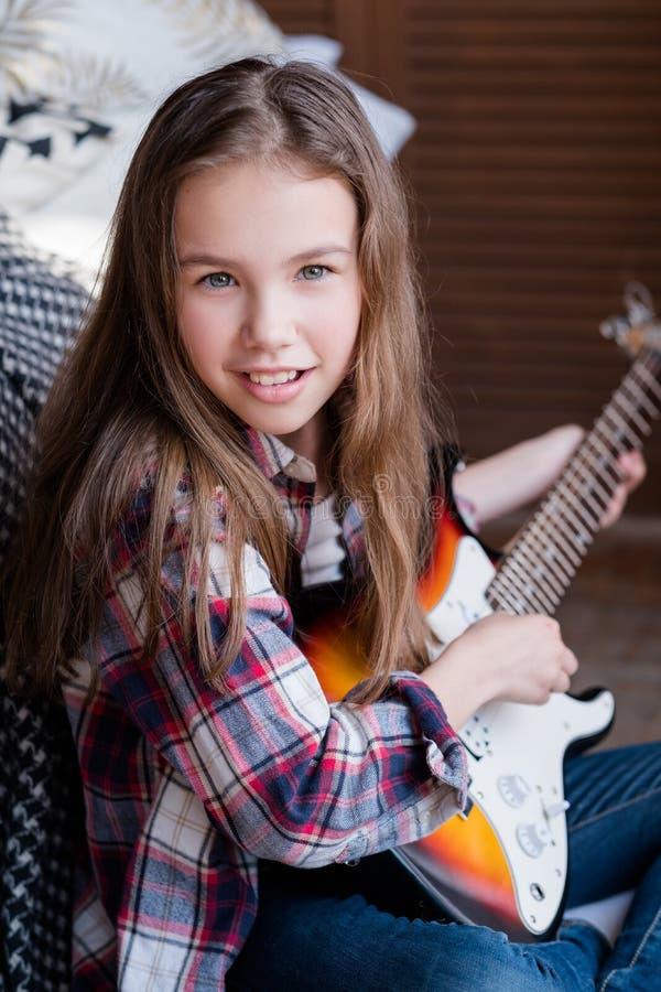 Flicka för barnkonstfritid som spelar gitarrmusikhobby royaltyfria bilder