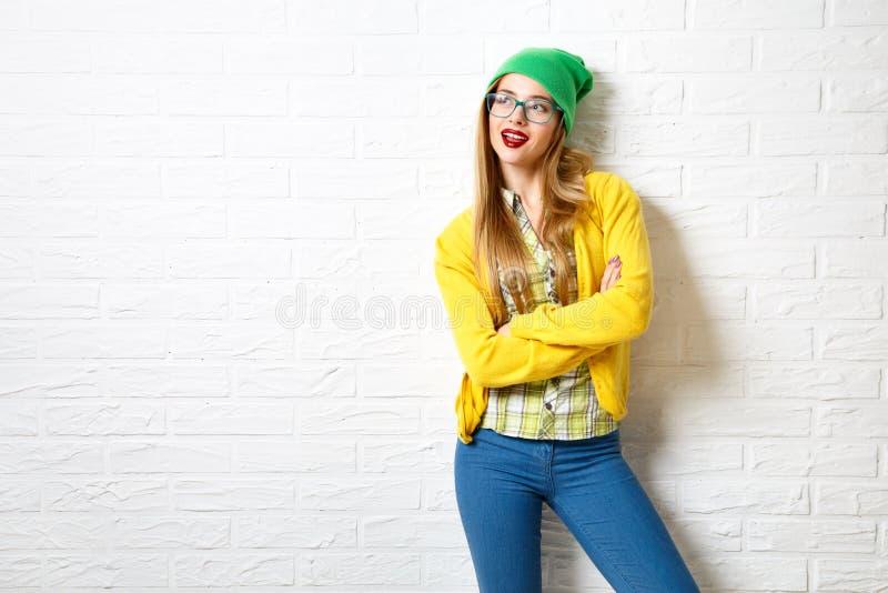 Flicka för gatastilHipster på vit bakgrund för tegelstenvägg fotografering för bildbyråer