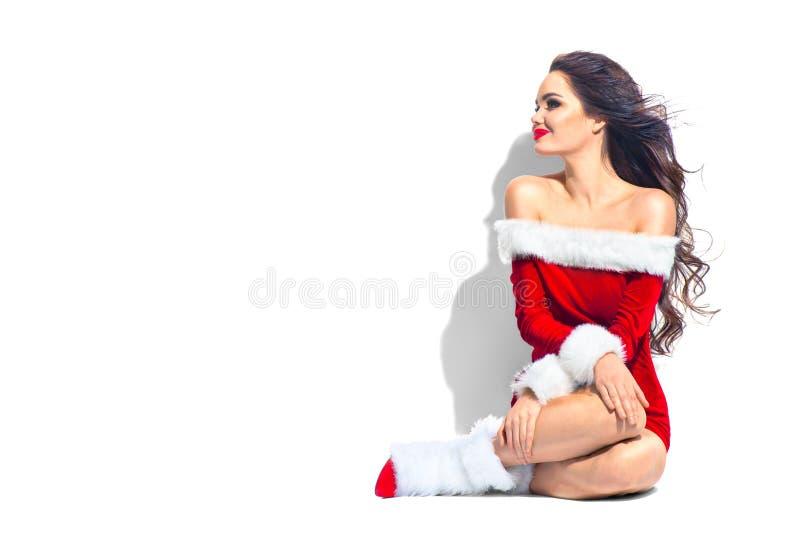 Flicka för julskönhetmodell Ung kvinna för sexig brunett som bär den röda klänningen royaltyfri bild
