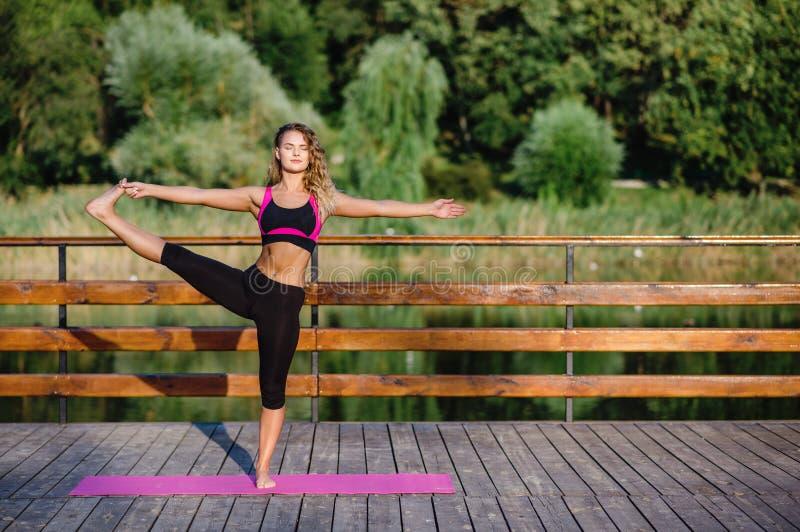 Flicka för konditionsportskönhet som gör yoga, kondition och sträcker övning i parkera arkivfoto