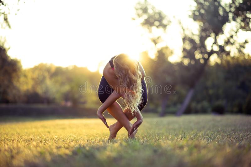 Flicka för konditionsportskönhet som gör yoga, kondition och sträcker övningen i parkera, utomhus- sportar arkivbilder