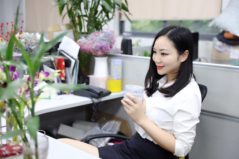 Flicka för kvinna för Asien kinesisk kontorsdam på för drinkte för stol tänkande arbetsplats för dräkt för ockupation för affär f royaltyfria bilder