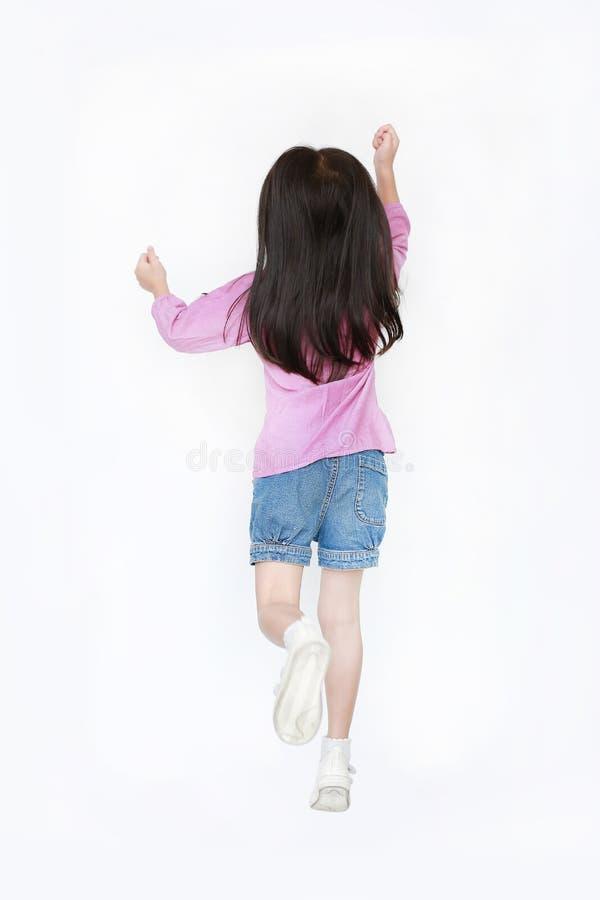 Flicka för liten unge för bakre sikt som hoppar över vit bakgrund Begrepp för frihetsungerörelse arkivbild