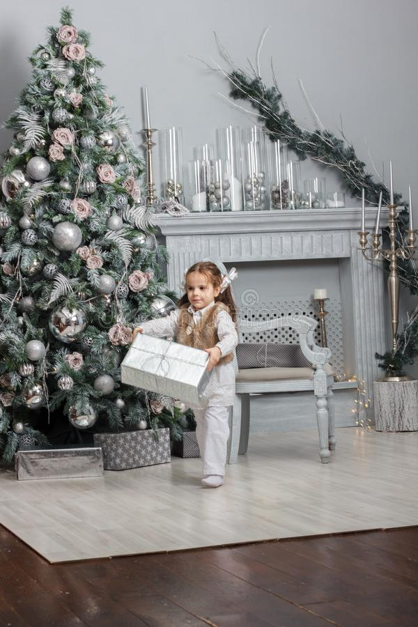 Flicka för liten unge som blir på rummet med julträdet och gåvor arkivfoton