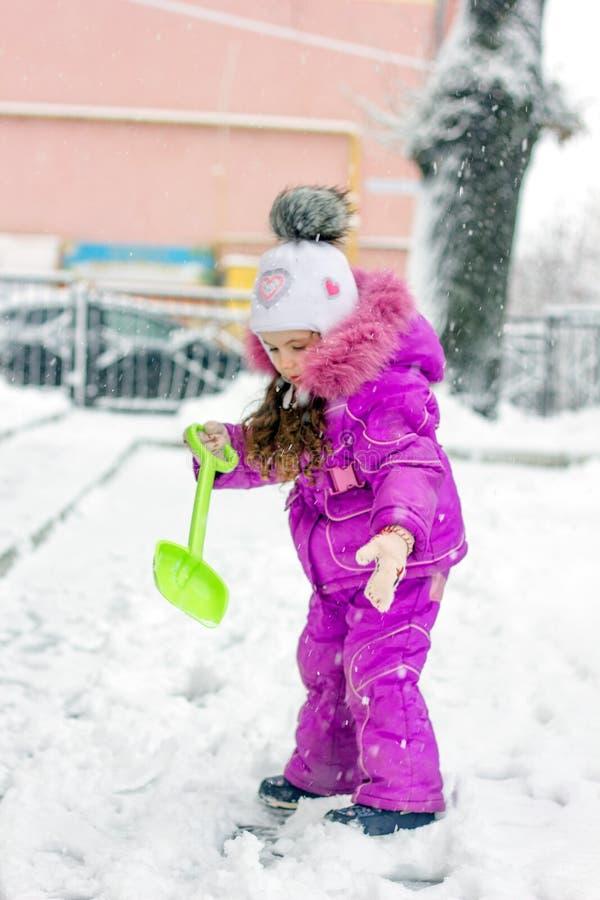 Flicka för liten unge som skyfflar snö på hem- drevväg fotografering för bildbyråer