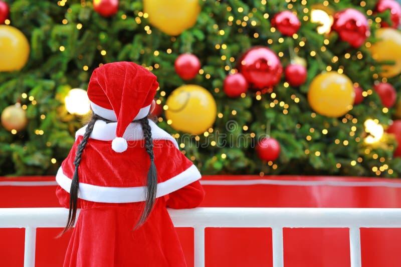 Flicka för litet barn för bakre sikt i jultomtendräkten som ser julgranen glad xmas för bakgrund royaltyfri foto