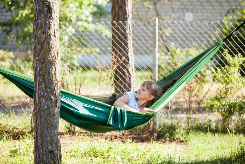 Flicka för litet barn som kopplar av i den gröna hängmattan och ler på den soliga sommardagen på utomhus- ferier i familjträdgård fotografering för bildbyråer