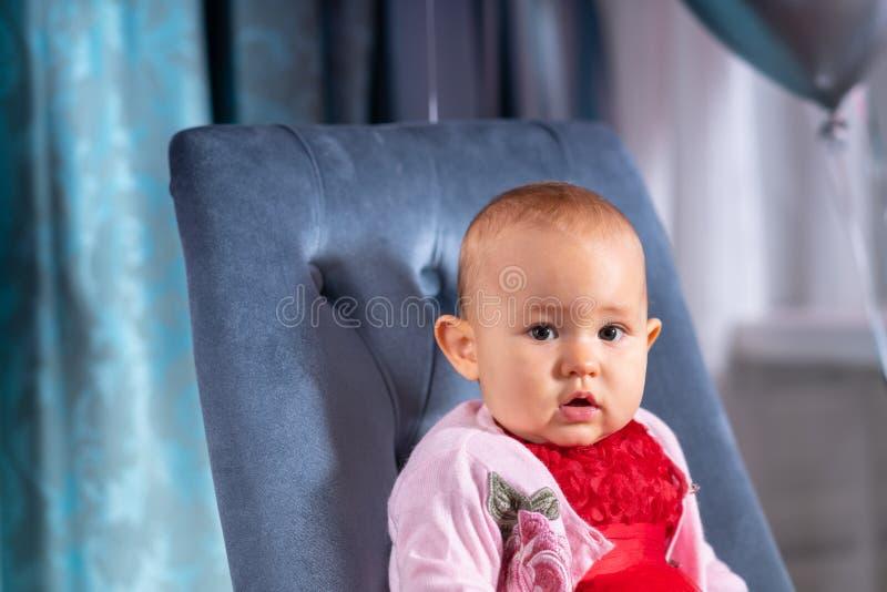 Flicka för litet barn som sitter på blå stol royaltyfri fotografi