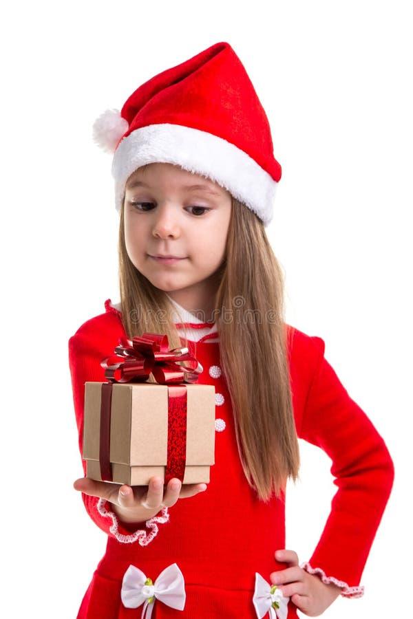 Flicka för lycklig jul som ser gåvan som rymmer det i handen som bär en santa hatt som isoleras över en vit bakgrund royaltyfri fotografi