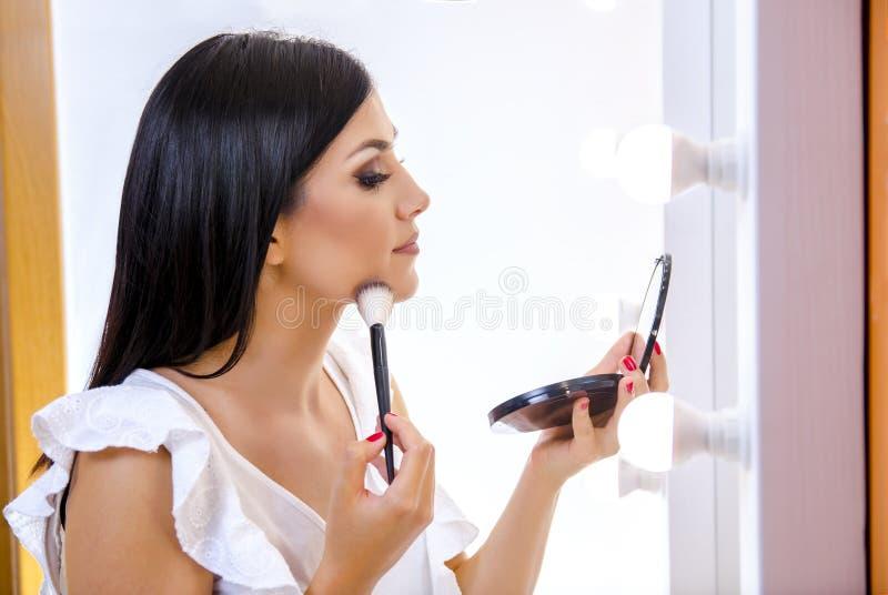 Flicka för mörkt hår för sidosikt som härlig sätter på makeup på royaltyfri bild