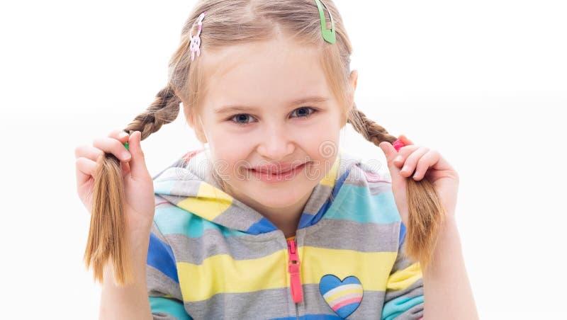 Flicka för skolaålder som spelar med hennes flätade råttsvansfrisyr arkivbild