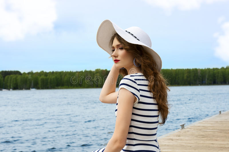 Flicka för sommarferier på sjövithatten royaltyfri fotografi