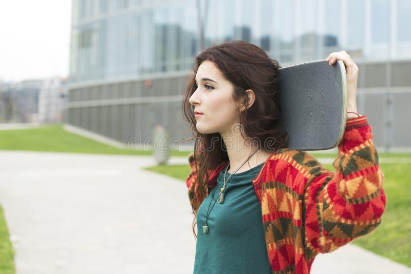 Flicka för stads- stående för Closeup härlig med skateboarden royaltyfria foton