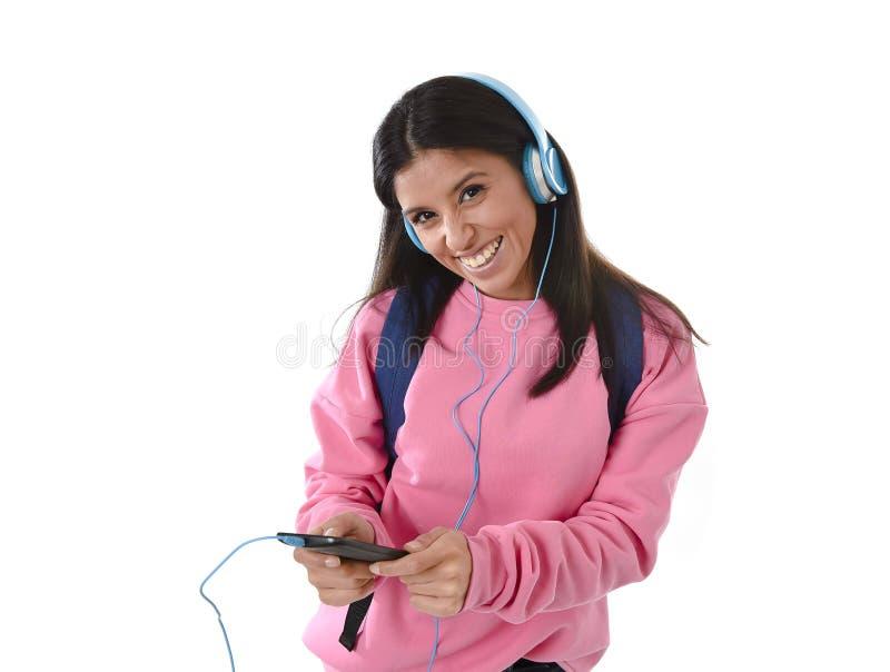 Flicka för ung kvinna eller studentmed mobiltelefonen som lyssnar till musikhörlurar som sjunger och dansar royaltyfri bild