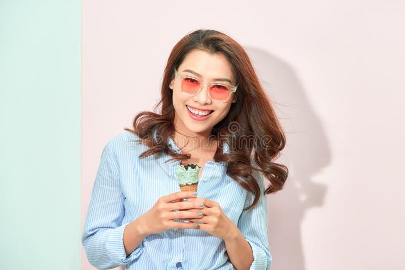 Flicka för ung kvinna i solglasögon som äter glass royaltyfri fotografi