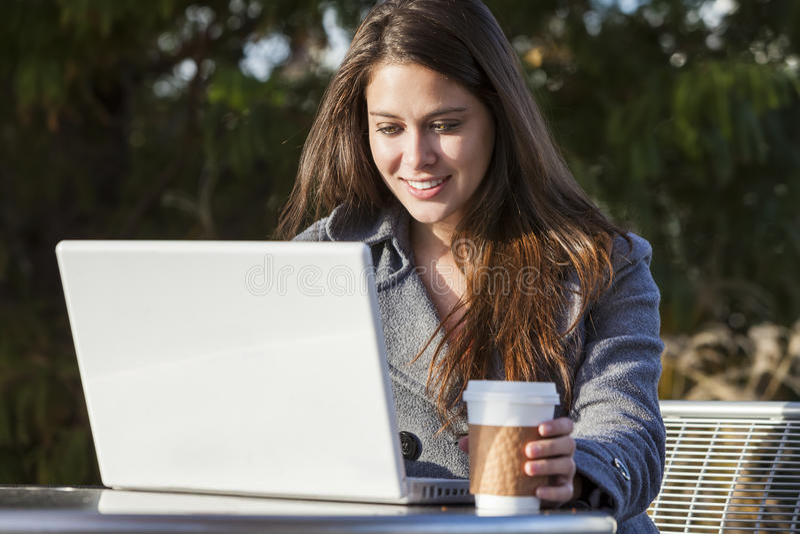 Flicka för ung kvinna som använder bärbara datorn som dricker kaffe royaltyfria bilder