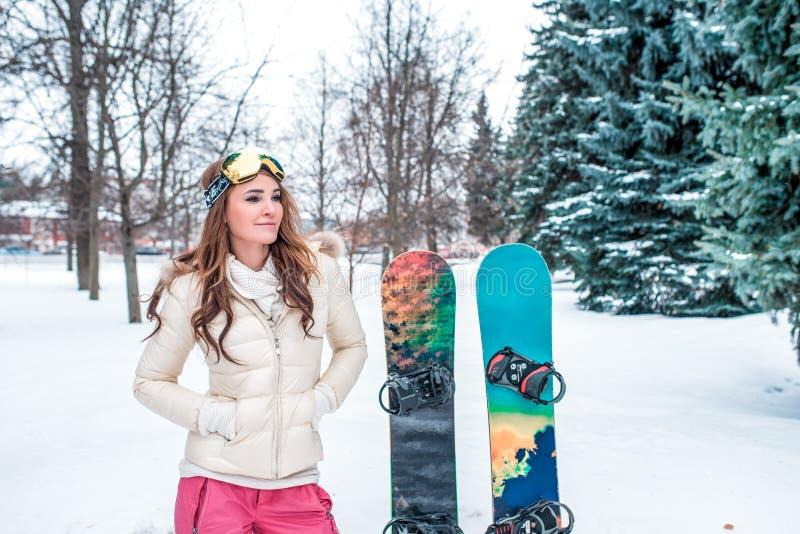 Flicka för vintersportar på en bakgrund av snö- och granträd Stå bredvid snowboards, fritt utrymme för text Ferie i a royaltyfria foton