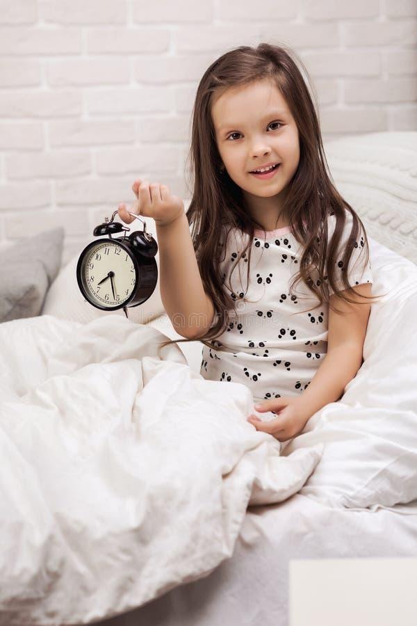 Flicka f?r litet barn i pyjamas med klockan arkivfoto