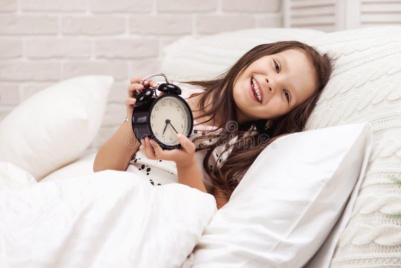 Flicka f?r litet barn i pyjamas med klockan arkivbilder
