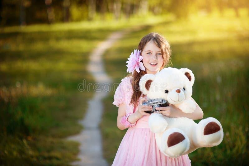 Flicka-fotografen i en rosa klänning som kramar en nallebjörn royaltyfri bild