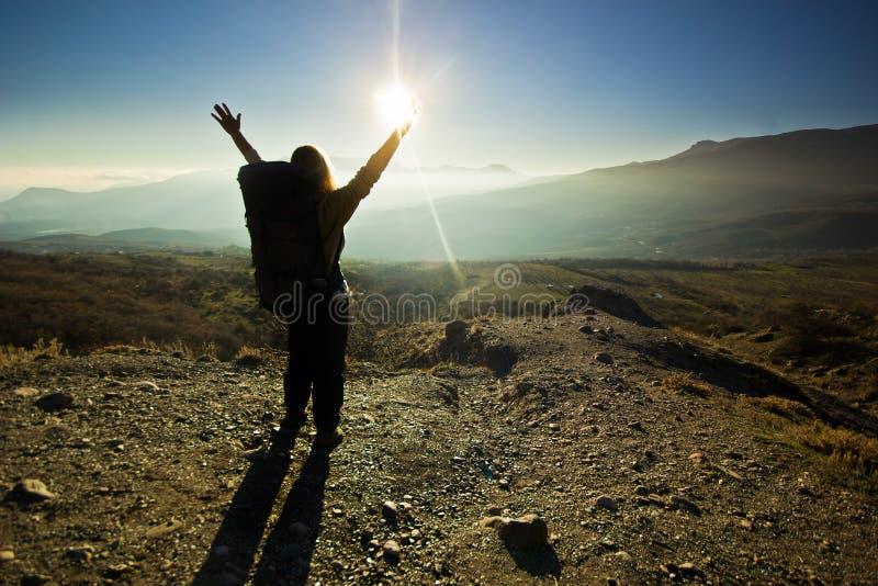 Flicka-fotvandrare med händer upp i bergen royaltyfri foto
