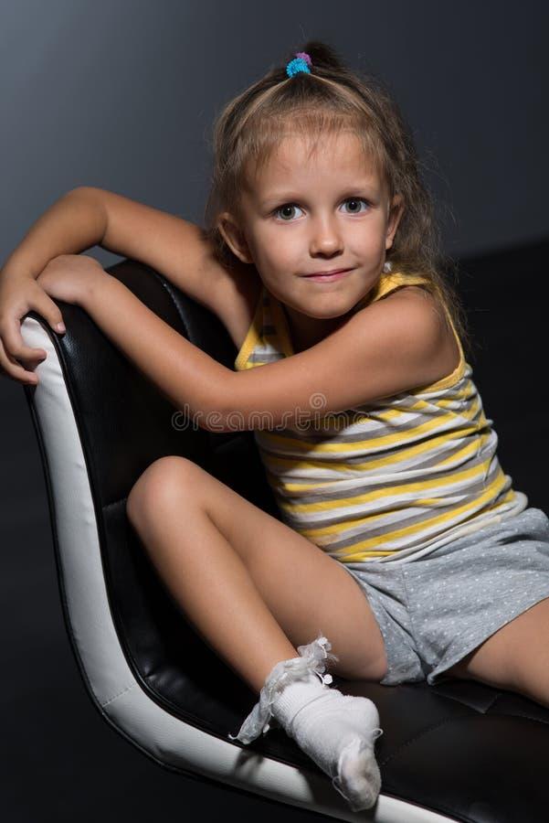 Flicka fyra år på en stol arkivbild