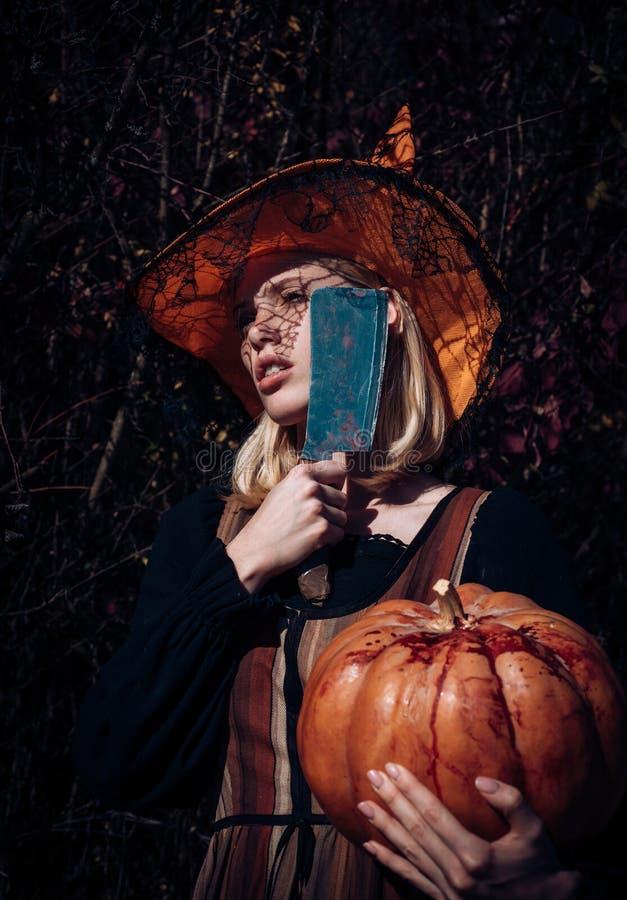 flicka halloween Kvinnadressing i allhelgonaaftondräkt med orange häxas hatt för ett themed parti Attraktivt häxainnehav arkivfoton