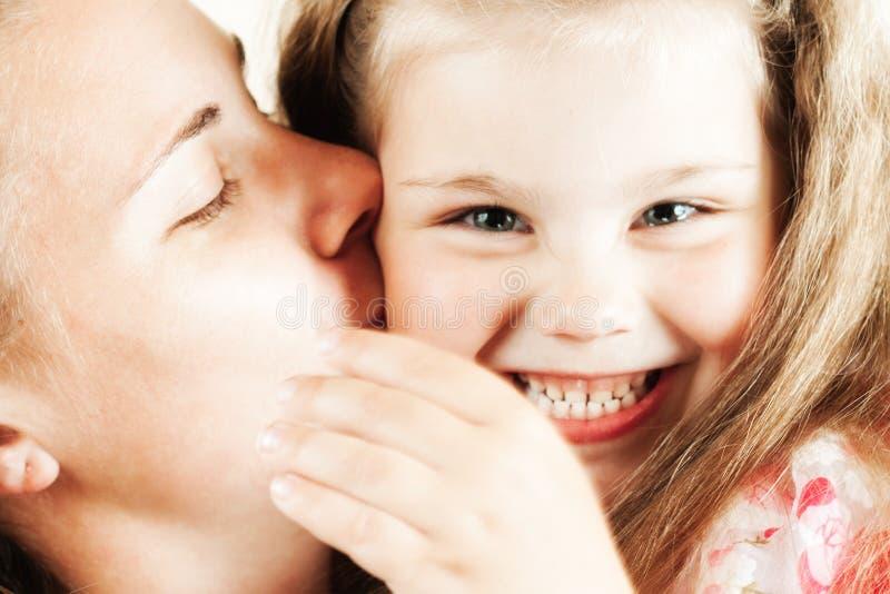 flicka henne kyssande moder royaltyfri fotografi