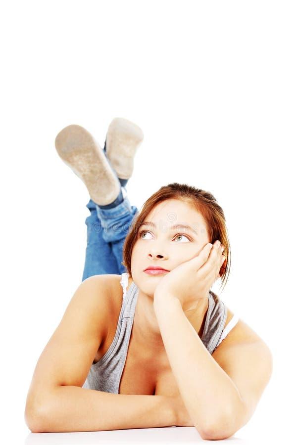 flicka henne liggande teen fundersam tummy arkivfoton