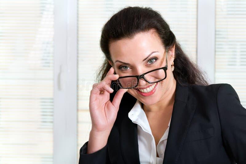 Flicka i affärsdress som ser över hans exponeringsglas och skratt royaltyfri bild