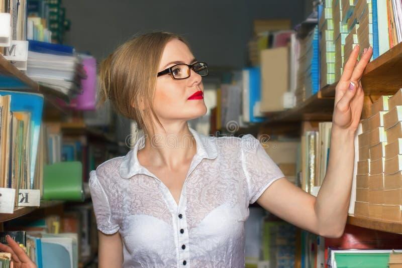 FLICKA I ARKIVET MELLAN kuggar med böcker som ser härligt b fotografering för bildbyråer