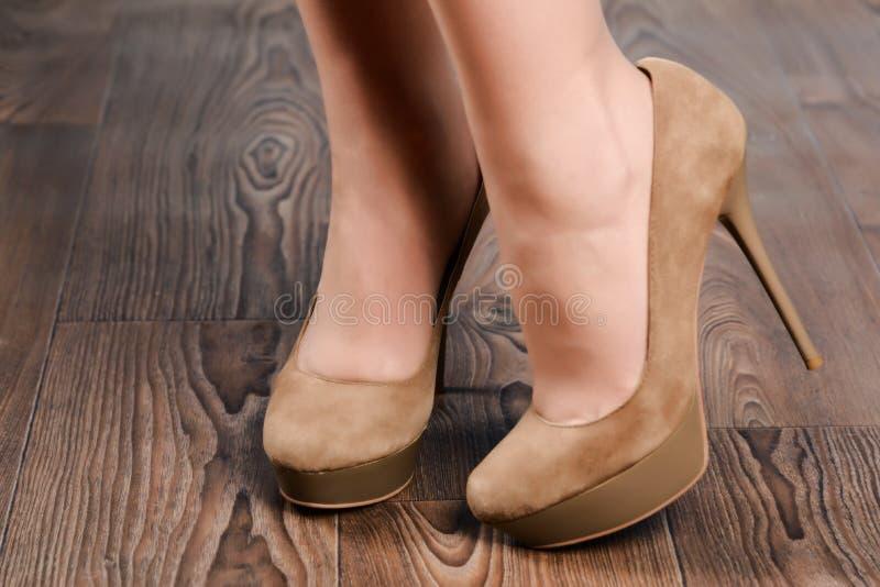 Flicka i beige mockaskinn hög-heeled skor royaltyfria bilder
