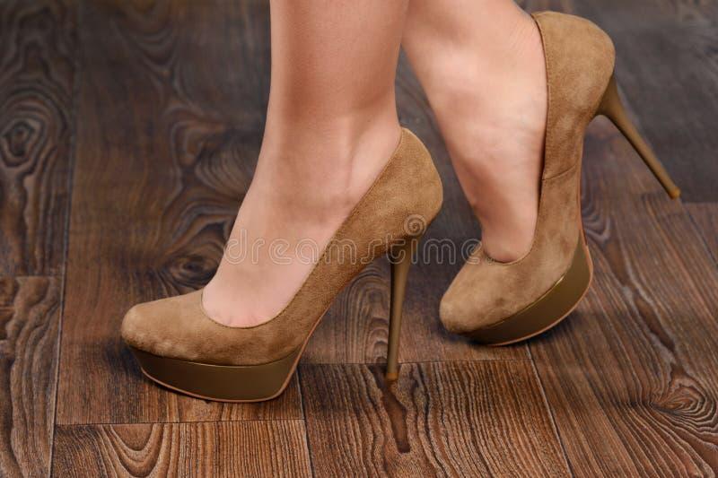 Flicka i beige mockaskinn hög-heeled skor fotografering för bildbyråer