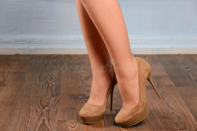 Flicka i beige mockaskinn hög-heeled skor royaltyfri bild