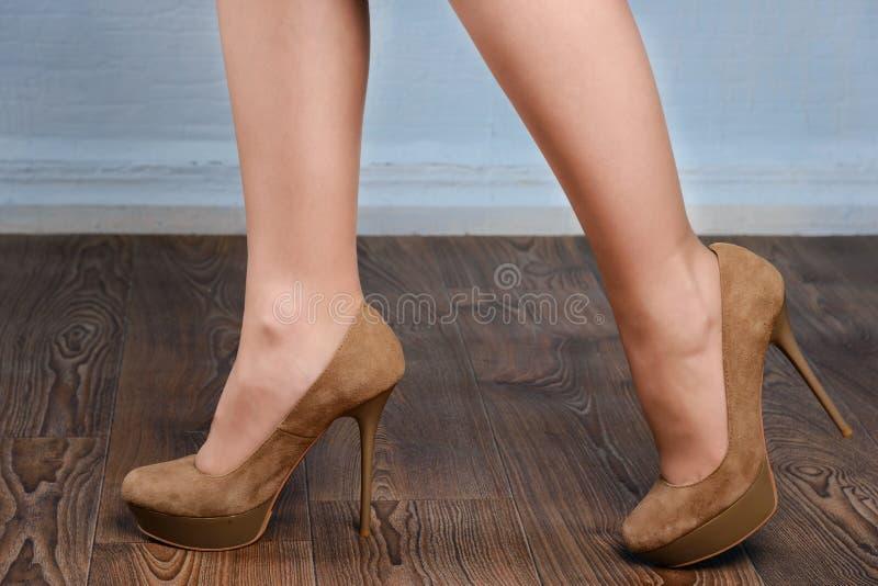 Flicka i beige mockaskinn hög-heeled skor arkivbild