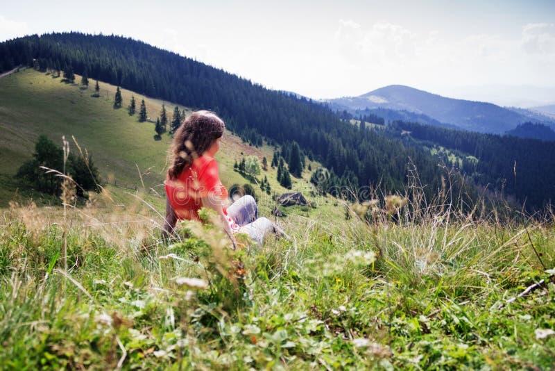 Flicka i bergen, en handelsresande som fotograferas från baksidan royaltyfri fotografi