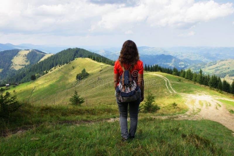 Flicka i bergen, en handelsresande som fotograferas från baksidan royaltyfria foton