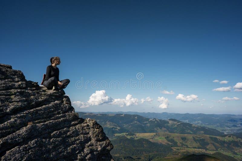 Flicka i bergen på en klippa som fotvandrar fotografering för bildbyråer