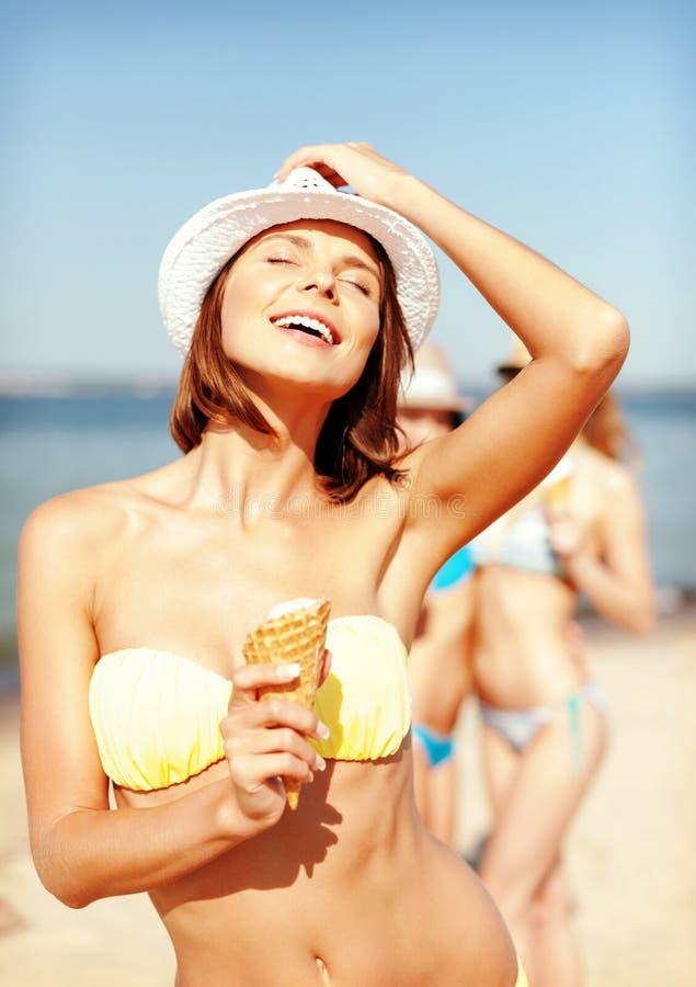 Flicka i bikini som äter glass på stranden arkivbilder