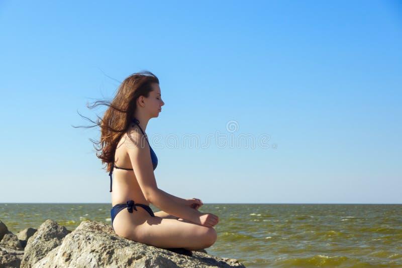 Flicka i bikini som kopplar av på havsstranden royaltyfria bilder