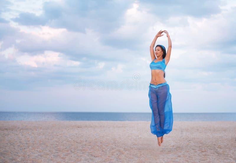 Flicka i blå magdansdräkt i luften royaltyfri foto