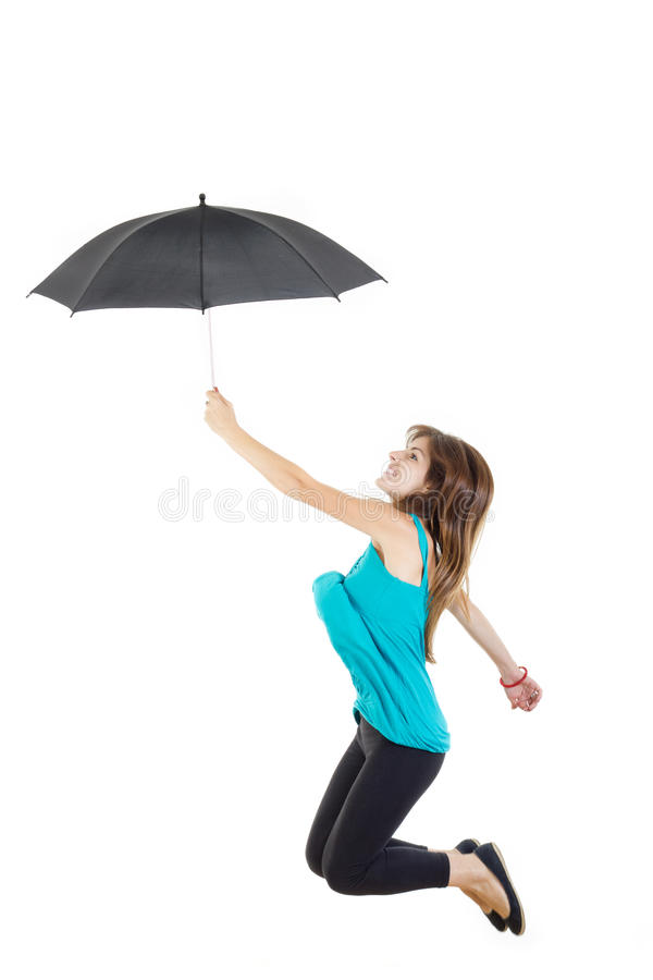 Flicka i blå t-skjorta och svart strumpbyxor med paraplybanhoppning arkivfoto