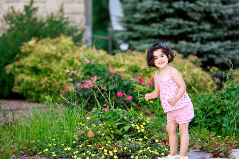 Flicka I Blommaträdgård Arkivbild